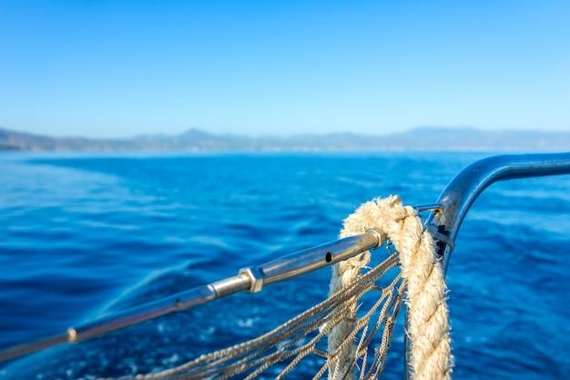 Zonnige zomerdag in de baai van de zee. achter de reling van een zeiljacht. het oude touw hangt aan de rail