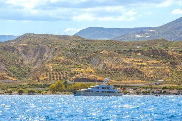 Zonnige zomerdag in de golf van korinthe. motorjacht op de achtergrond van een klein stadje aan een bergachtige kust. uitzicht vanaf het water