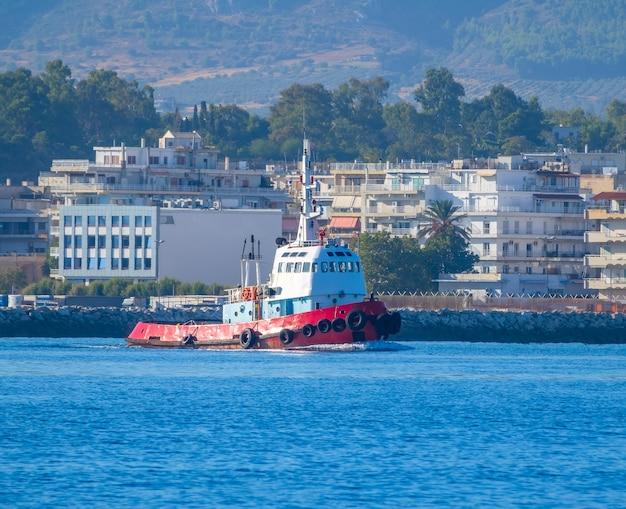 Zonnige zomerdag in de golf van korinthe. sleepboot op de achtergrond van een kleine stad