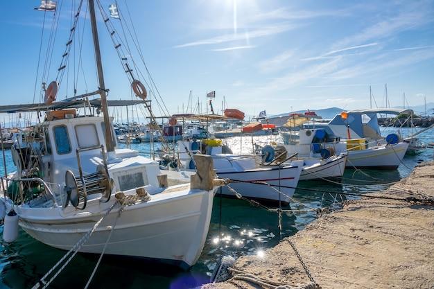 Zonnige zomerdag in de jachthaven van de griekse stad. veel oude vissersboten bij de pier