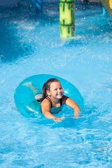 Zonnige zomerdag in waterpark klein gelukkig meisje zwemt in helder blauw water van zwembad in opblaasbare wrijf...