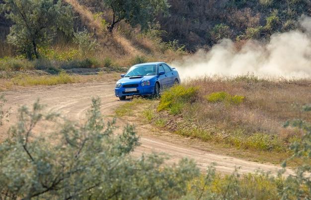 Zonnige zomerdag. onverharde weg voor de rally. auto rijdt door een bocht en maakt veel stof