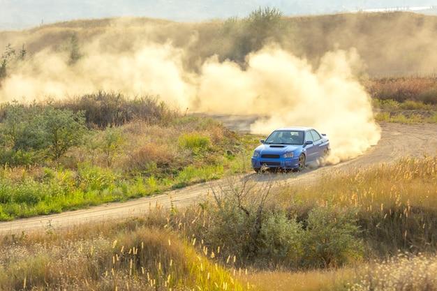 Zonnige zomerdag. onverharde weg voor de rally. een auto rijdt door een bocht en maakt veel stof 02