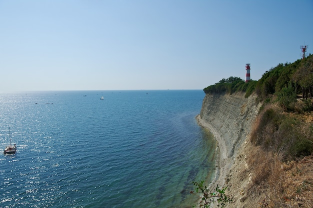 Zonnige zomerdag. oude vuurtoren zwarte zee rotsachtige kust