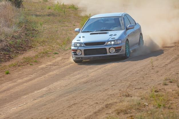 Zonnige zomerdag. stoffige rallybaan. sportwagen doet op zijn beurt veel stof 02