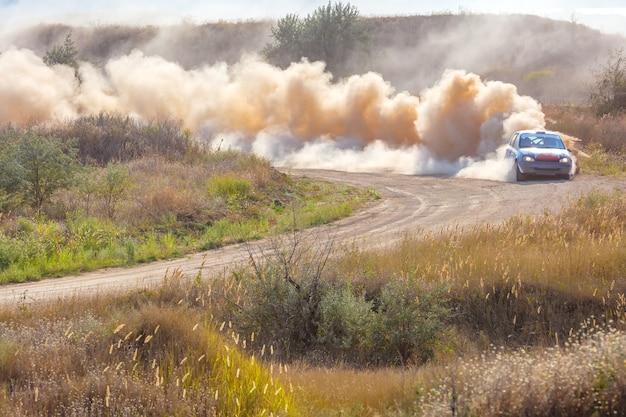 Zonnige zomerdag. stoffige rallybaan. sportwagen doet op zijn beurt veel stof 05