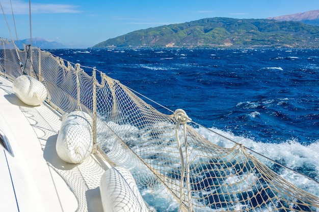 Zonnige zomerdag. winderig weer nabij de kust van de golf van korinthe. dek van een wit zeiljacht met spatborden