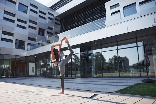 Zonnige zomerochtend. jonge atletische vrouw die handstand op de straat van het stadspark onder moderne stedelijke gebouwen doen. oefening buitenshuis gezonde levensstijl