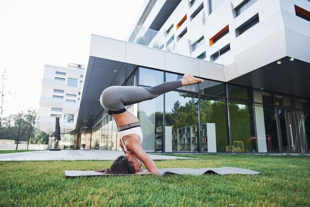 Zonnige zomerochtend. jonge atletische vrouw doet handstand op stadspark straat onder moderne stedelijke gebouwen. sport buitenshuis een gezonde levensstijl.