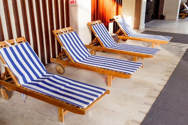 Zonovergoten openbaar zwembadbinnenland met chaise-longues