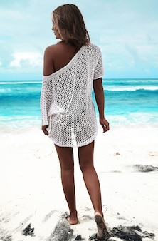 Zonovergoten vrouw in transparante witte blouse lopen op zomer strand