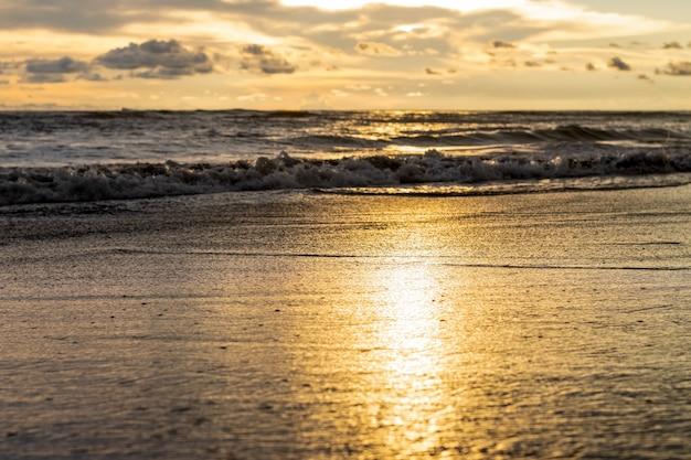 Zonreflectie op het zeestrand met de ondiepe focus in de avond