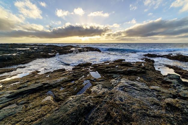 Zonsondergang aan de zeekust met grote rotsen gewassen door de golven, lucht met wolken in gouden tinten en reflecties in het water tussen de rotsen. spanje. europa.