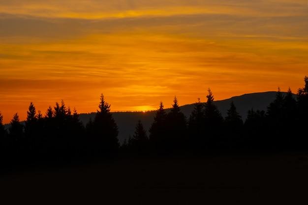 Zonsondergang berg hemel blauw kleurrijke herfst zon licht geel oranje wolken boom rook mist nevel