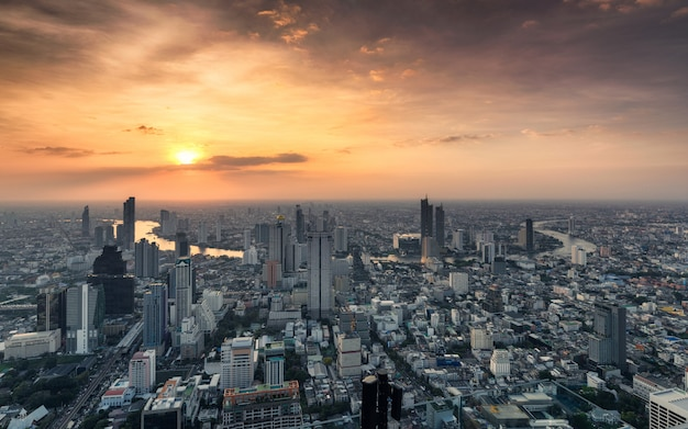 Zonsondergang bij de overvolle bouw met chao phraya-rivier bij de stad van bangkok, thailand