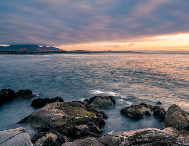 Zonsondergang bij ritoque-strand op een bewolkte dag met een berg achter