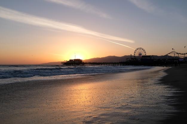 Zonsondergang bij santa monica beach, californië. de gouden kleur van het zand. hoge kwaliteit foto