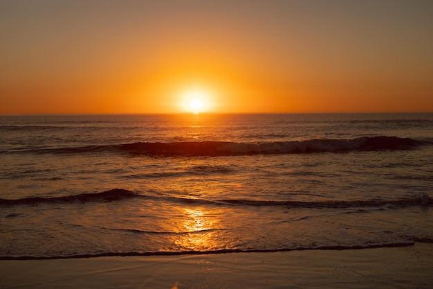 Zonsondergang boven de zee op het strand