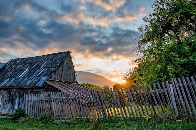 Zonsondergang boven het huis en groene bomen op het platteland