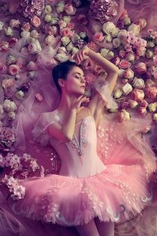 Zonsondergang. bovenaanzicht van mooie jonge vrouw in roze ballet tutu omgeven door bloemen. lentestemming en tederheid in koraallicht. kunst foto. concept van de lente, bloesem en het ontwaken van de natuur.