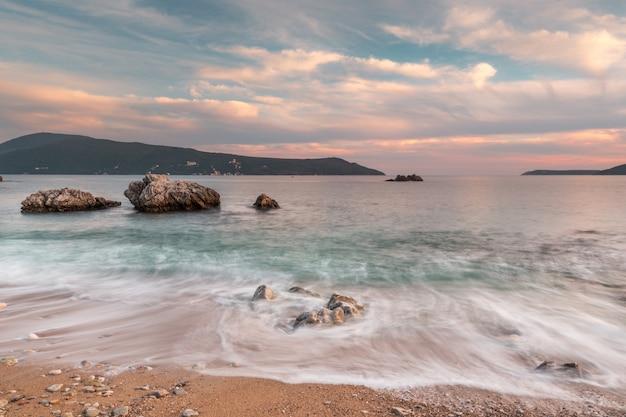 Zonsondergang en golven aan de kust.