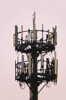 Zonsondergang en lange mast met cellulaire antenne