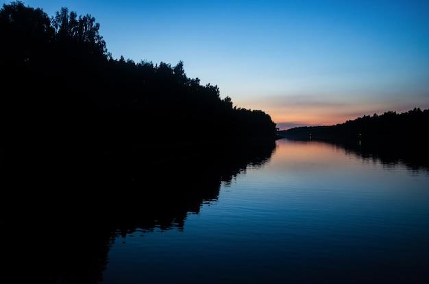 Zonsondergang en zijn reflectie op het wateroppervlak van de rivier heldere kleuren en silhouetten van bomen