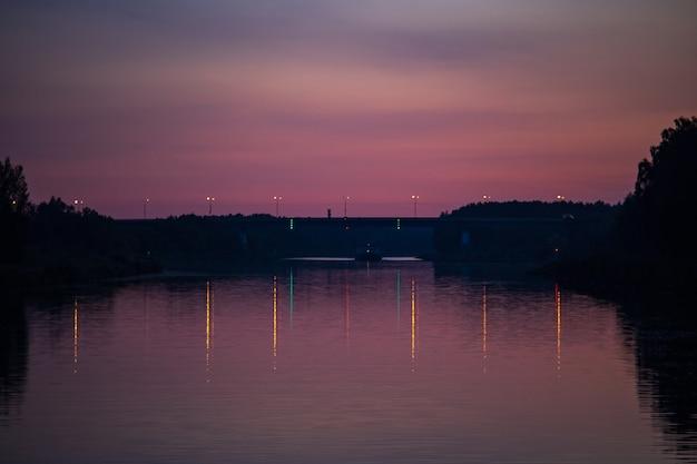 Zonsondergang en zijn weerspiegeling op het wateroppervlak van de rivier silhouetten van bomen ruimte kopiëren