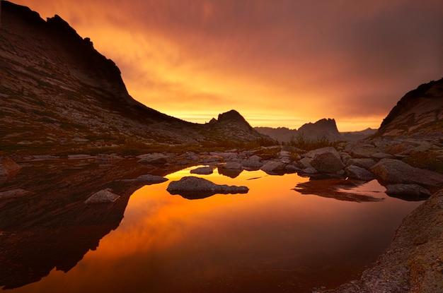 Zonsondergang in bergen dichtbij meer, weerspiegeld zonlicht