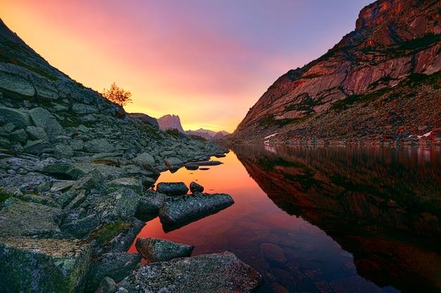 Zonsondergang in bergen dichtbij meer. zonlicht weerspiegeld op bergtoppen. gouden licht uit de lucht weerspiegeld