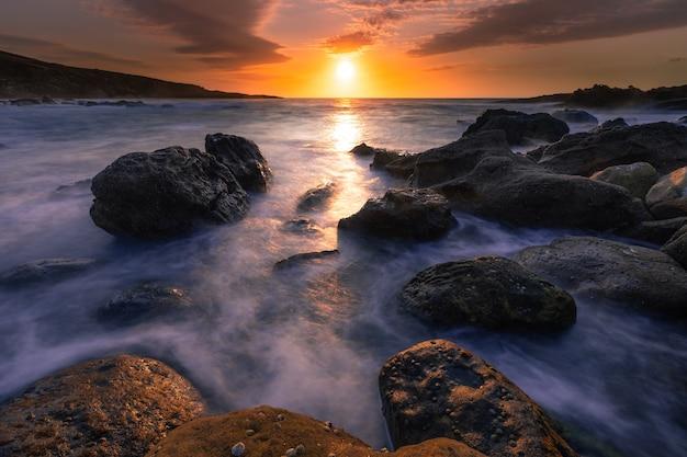 Zonsondergang in de baskische kust onder berg jaizkibel in hondarribia, baskenland.