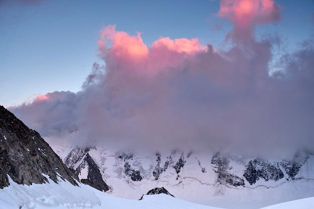 Zonsondergang in de bergen. bezinning van rode zon op de pieken en de wolken van de bergsneeuw. altai, belukha en omgeving