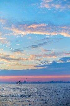 Zonsondergang in de bosporus. een schip vaart in het water.