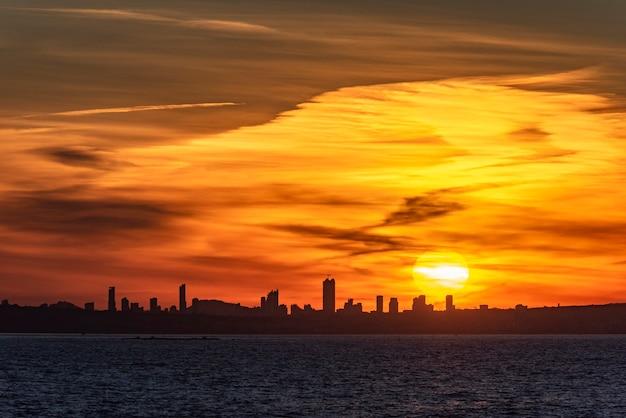 Zonsondergang in de stad benidorm, met een blauwachtige zee.
