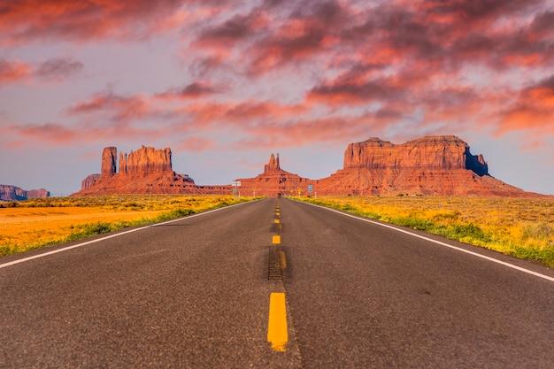 Zonsondergang in de weg met zijn gele lijnen van monument valley, utah