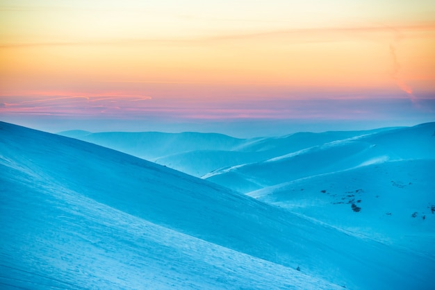 Zonsondergang in de winterbergen die met sneeuw worden bedekt