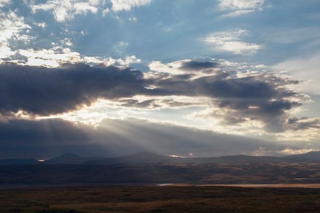 Zonsondergang in de woestijn, de zonnestralen schijnen door de wolken