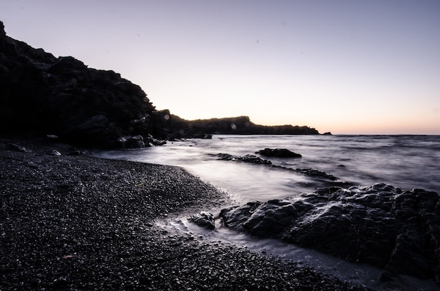 Zonsondergang in een steenstrand