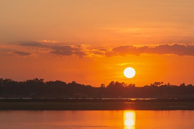 Zonsondergang in het meer. prachtige zonsondergang achter de wolken boven de meer landschap achtergrond. dramatische hemel met wolk bij zonsondergang