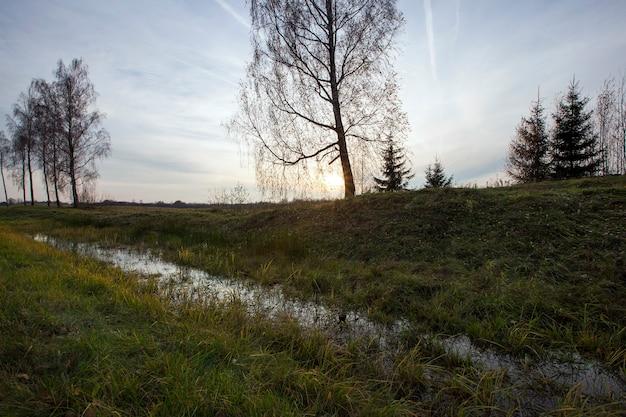 Zonsondergang in het veld met water, landschap in de late herfst bij bewolkt weer