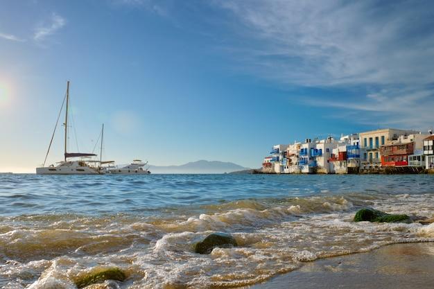 Zonsondergang in mykonos, griekenland, met cruiseschip en jachten in de haven