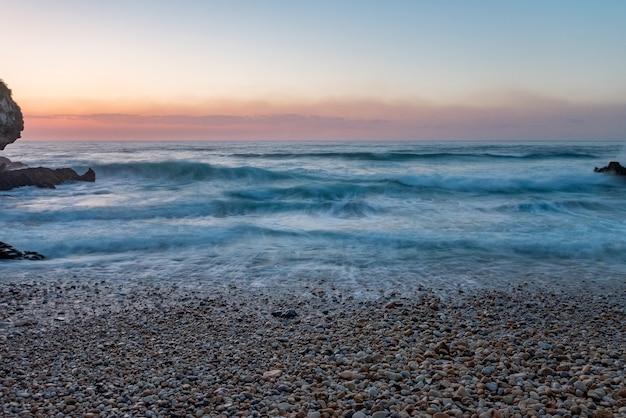 Zonsondergang in vidiago strand in llanes, asturias, spanje