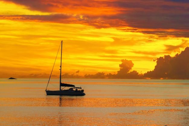 Zonsondergang in zee en zeiljacht silhouet