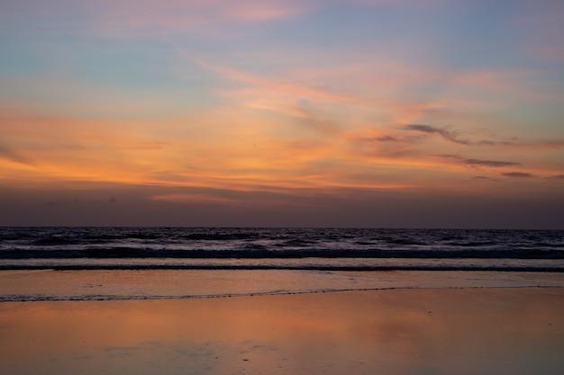 Zonsondergang met de golven die op het strand breken