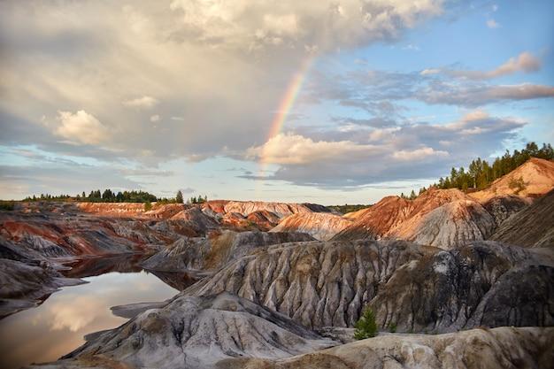 Zonsondergang met een regenboog in de zandheuvels
