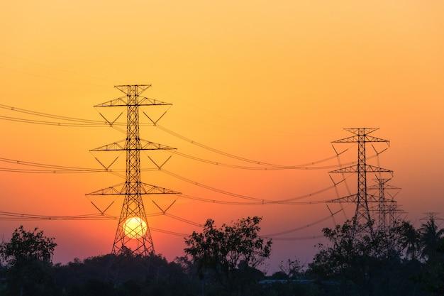 Zonsondergang met hoogspanning elektrische polen in het midden van rijstvelden in de avond.