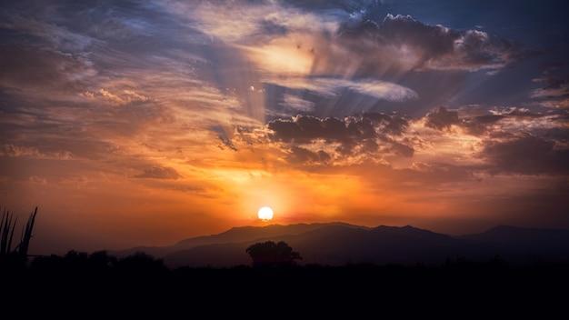 Zonsondergang met stralen tussen de wolken en de horizon op de achtergrond. kleuren bruin, oranje en blauw.