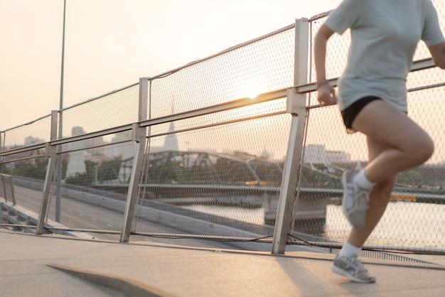 Zonsondergang met vrouw die voor oefening loopt Premium Foto