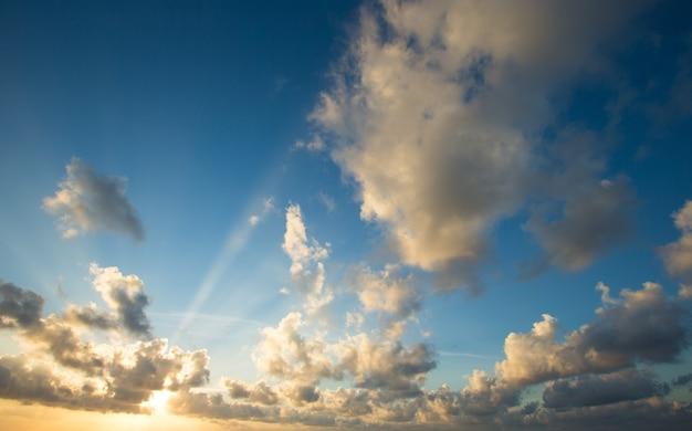 Zonsondergang met zonnestralen, hemel met wolken en zon