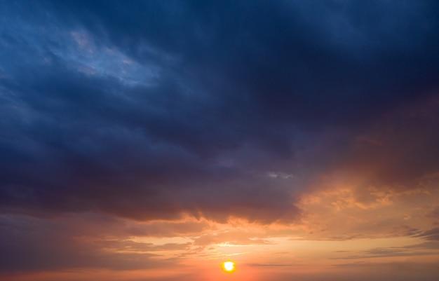 Zonsondergang met zonnestralen, lucht met wolken en zon.